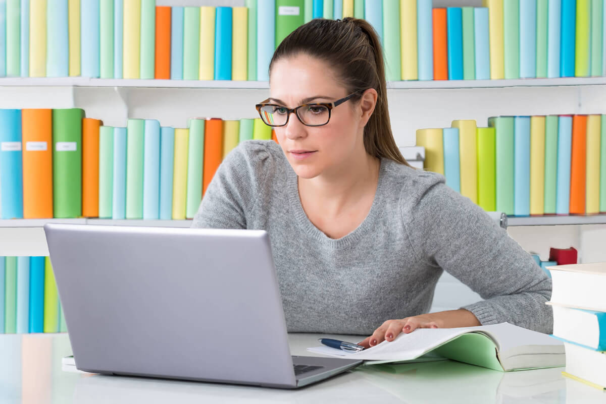 Young Woman Sitting In Library Using Laptop